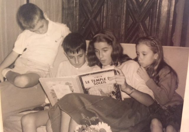 A young Mimi reading to her family